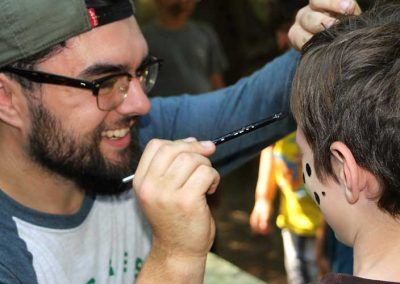 Counselor painting camper's face